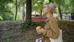 Jonge mooie vrouw met de korte koffie van de kapselholding en het typen op telefoon, die in park lopen stock video