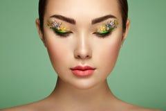 Jonge mooie vrouw met de ogen van de bloemmake-up royalty-vrije stock foto