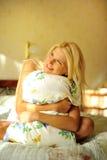 Jonge mooie vrouw met een hoofdkussen op haar bed Stock Afbeeldingen