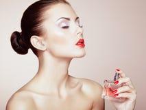 Jonge mooie vrouw met fles parfum. Perfecte Make-up Stock Afbeeldingen