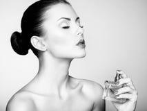Jonge mooie vrouw met fles parfum. Perfecte Make-up Stock Afbeelding