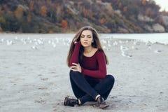 Jonge mooie vrouw met gesloten ogen, lang haar, die zwarte jeans en rood overhemd dragen, die op zand op strand onder zeemeeuwen  Royalty-vrije Stock Foto's