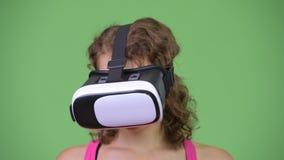 Jonge mooie vrouw met krullend blond haar die virtuele werkelijkheidshoofdtelefoon met behulp van stock videobeelden