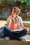 Jonge mooie vrouw met krullend haar die en in ex denken schrijven Stock Fotografie