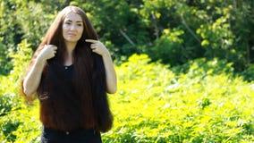 Jonge mooie vrouw met lang haar in openlucht Hairstyl Portret van een meisje met bruin haar stock footage