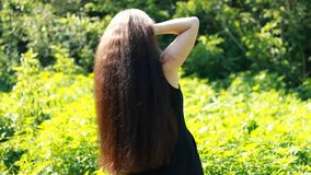 Jonge mooie vrouw met lang haar in openlucht hairstyle stock videobeelden