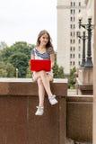 Jonge mooie vrouw met laptop zitting op treden dichtbij de universiteit Stock Foto