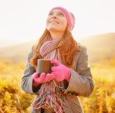 Jonge mooie vrouw met mok het in hand bekijken de de herfsthemel stock foto