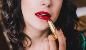 Jonge mooie vrouw met perfecte huid die rode lippenstift gebruiken Royalty-vrije Stock Afbeelding