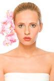 Jonge mooie vrouw met roze orchideeën in haar Royalty-vrije Stock Foto's