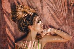 Jonge mooie vrouw met schaduwen op gezicht met gesloten ogen royalty-vrije stock afbeelding