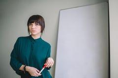 Jonge mooie vrouw met teller die of tribunes schrijven trekken bij whiteboard Bedrijfs concept royalty-vrije stock afbeelding