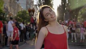 Jonge mooie vrouw met zich op straat tijdens festival bevinden, in camera en gemberhaar die, menigte van ventilators kijken gliml stock videobeelden