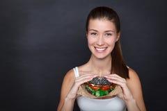 Jonge mooie vrouw met zwarte hamburger in haar handen op de donkere grijze achtergrond studio Royalty-vrije Stock Foto