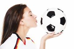 Jonge mooie vrouw ongeveer om een voetbal te kussen Royalty-vrije Stock Afbeeldingen