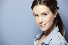 Jonge mooie vrouw op blauwe achtergrond Royalty-vrije Stock Fotografie