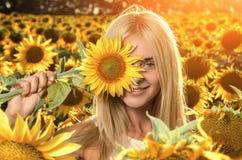 Jonge mooie vrouw op bloeiend zonnebloemgebied stock foto
