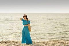 Jonge mooie vrouw op het strand in azuurblauwe lange kleding met mobi Royalty-vrije Stock Fotografie