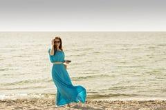 Jonge mooie vrouw op het strand in azuurblauwe lange kleding met mobi Stock Afbeeldingen