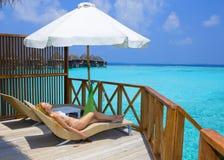 Jonge mooie vrouw op platform bij villa op water, Royalty-vrije Stock Foto