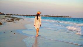 Jonge mooie vrouw op tropische kust in zonsondergang Gelukkig meisje in kleding in de avond op het strand langzame geanimeerde vi stock video