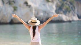 Jonge mooie vrouw op wit zand tropisch strand Kaukasisch meisje op hoedenachtergrond het overzees stock footage