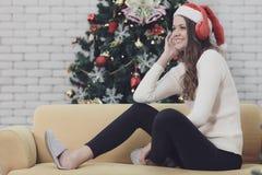Jonge mooie vrouw in rode hoedenzitting op bank tussen christm royalty-vrije stock afbeeldingen