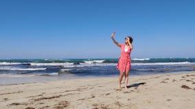 Jonge mooie vrouw in rode kleding die selfie met haar cameratelefoon nemen op het overzeese strand met sterke wind en golven stock video