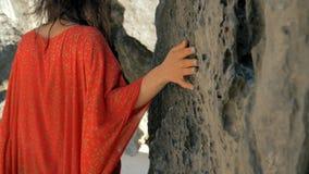 Jonge mooie vrouw in rode kledings vindende vingers over steen op strand op zonnige dag Vrouwen glijdende hand tegen steen binnen stock videobeelden