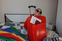 Jonge mooie vrouw, rode koffer die, zitting, wachten, de zomervakantie, kleurrijk, rond wereld reizen Stock Afbeeldingen