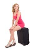 Jonge mooie vrouw in roze kledingszitting op grote koffer over Royalty-vrije Stock Fotografie