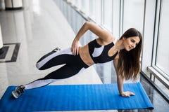 Jonge mooie vrouw in sportkleding die zijplank doen en camera voor venster gymnastiek bekijken royalty-vrije stock afbeeldingen