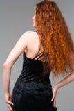 Jonge mooie vrouw in zwarte kleding met lange rode haren touchin royalty-vrije stock afbeeldingen