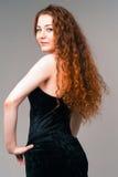 Jonge mooie vrouw in zwarte kleding met lange rode harenvervanger stock afbeelding