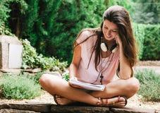 Jonge mooie vrouwelijke buiten en zitting die bestuderen Royalty-vrije Stock Afbeeldingen
