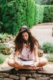 Jonge mooie vrouwelijke buiten en zitting die bestuderen Stock Foto's