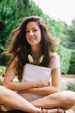 Jonge mooie vrouwelijke buiten en zitting die bestuderen Royalty-vrije Stock Foto's