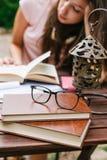 Jonge mooie vrouwelijke buiten en zitting die hard bestuderen Royalty-vrije Stock Foto