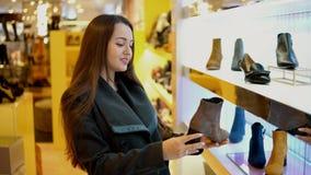 Jonge mooie vrouwelijke klant die de laarzen van Vrouwen in een opslagsupermarkt kiezen stock video