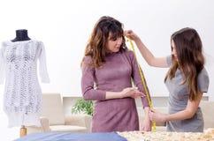 Jonge mooie vrouwelijke kleermaker die metingen nemen stock afbeeldingen