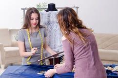 Jonge mooie vrouwelijke kleermaker die metingen nemen royalty-vrije stock foto