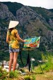 Jonge mooie vrouwelijke kunstenaar die Oude Kotor, Montenegro, op bergachtergrond schilderen Royalty-vrije Stock Afbeeldingen