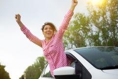Jonge mooie vrouwen drijfauto en het leunen uit autoraam reizend door auto, de zomervakantie royalty-vrije stock foto