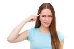 Jonge mooie vrouwen gesturing vinger tegen haar tempel Geïsoleerd op wit Stock Foto's