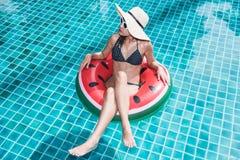Jonge mooie vrouwenbikini in de opblaasbare watermeloen van de ringsvlotter royalty-vrije stock afbeeldingen