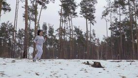 Jonge mooie vrouwenlooppas in de winterbos op in het hele land stock video