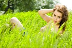 Jonge mooie vrouwenmijmerij in gras Stock Foto's