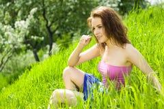 Jonge mooie vrouwenmijmerij in gras Stock Afbeeldingen