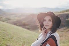 Jonge mooie vrouwenreiziger die hoed en poncho het ontspannen op de bovenkant van de heuvel dragen Stock Foto's