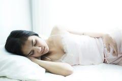 Jonge mooie vrouwenslaap op bed Royalty-vrije Stock Afbeelding